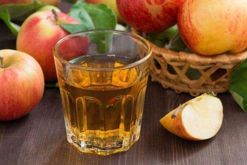 Ein Getränk aus Apfelessig, das gegen starke Menstruationblutungen hilft, steht vor einigen Äpfeln auf einem Tisch.